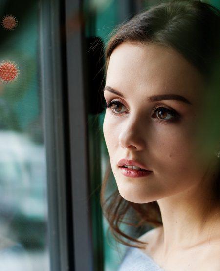 vrouw met spiegelbeeld van vrouw met mondkapje